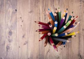 Crayons de couleur en bois, dans un bécher en cuir marron, vu de dessus, avec fond en bois