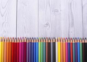 Crayons de couleur en bois vu du dessus sur un fond en bois gris et blanc