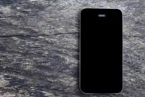 Vue de dessus du smartphone mobile écran noir maquette sur fond de table en bois ancienne vierge. vue aérienne téléphone plat poser et copier l'espace pour le concept d'entreprise.