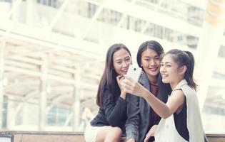femme heureuse avec des amis à l'aide de téléphone prendre une photo