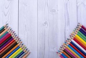 crayons de couleur en bois, dans les coins inférieurs d'un fond en bois blanc et gris
