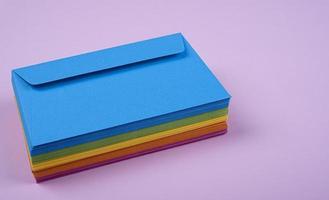 enveloppes colorées empilées sur fond rose clair
