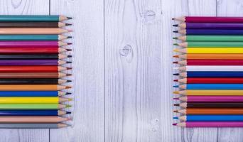 Crayons de couleur en bois, face à face, sur fond de bois gris et blanc