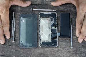 Vue de dessus du technicien de la main avec un tournevis réparation de téléphone portable à l'intérieur d'un téléphone portable avec une batterie de fixation d'un centre de service après-vente cassé sur une table en bois. concept de maintenance de smartphone. photo