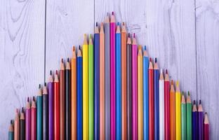 Crayons de couleur en bois, formant un triangle, sur un fond en bois blanc et gris
