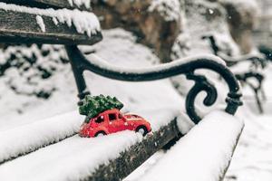 Voiture jouet rouge transportant un arbre de Noël sur le toit photo