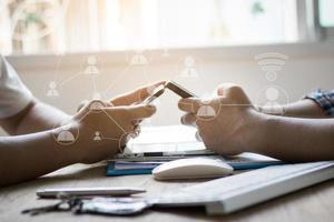 Groupe de personnes utilisent le téléphone sur la table en bois pour connecter et communiquer le concept photo