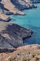 Bateau blanc sur la mer près de la formation de roche brune pendant la journée photo