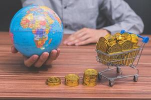 main tenant un globe et des pièces sur le bureau photo