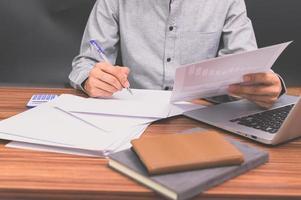 les gens d'affaires s'assoient au travail et vérifient les documents au bureau dans la chambre photo