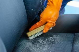 brosser le siège auto avec des gants orange