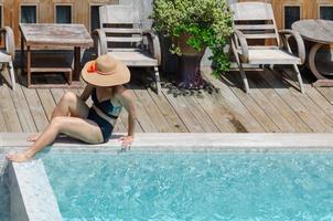 personne assise au bord de la piscine