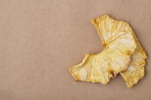 Vue de dessus des tranches d'ananas séchées isolés sur fond de texture de papier brun avec espace de copie