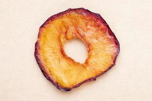 Vue de dessus de la tranche de prune séchée isolée sur fond de texture de papier brun photo