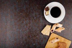 Vue de dessus de biscuits à la farine avec de la confiture de fraises sur une planche de bois et des morceaux de kozinaki au sésame et une tasse de café sur fond noir avec copie espace