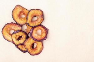 Vue de dessus des tranches de prune séchées isolés sur fond de texture de papier brun avec espace copie