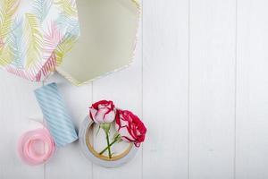 Vue de dessus de la boîte-cadeau et des roses de couleur rouge avec des rouleaux de ruban adhésif sur fond de bois blanc avec espace copie photo