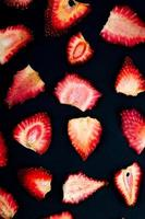 Vue de dessus des tranches de fraises séchées sur fond noir