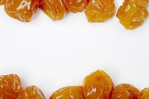 Vue de dessus des prunes cerises séchées sur fond blanc avec espace copie photo