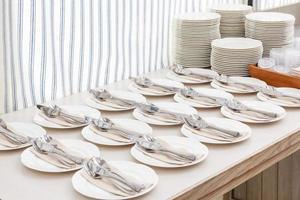 Des piles de plat blanc nettoyé pour buffet de restauration dans la salle de restaurant photo