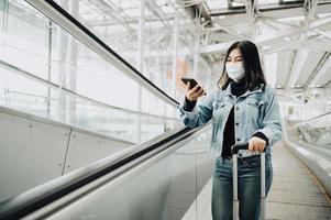 femme sur un escalator portant un masque et tenant un téléphone