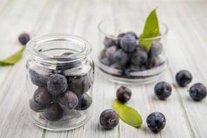 Vue de dessus des petits prunelles bleu-noir aigre sur un bocal en verre avec prunelles sur un bol en verre sur un fond de bois gris photo