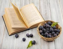 Vue de dessus des petits prunelles bleu-noir aigre sur un seau sur un fond en bois gris photo