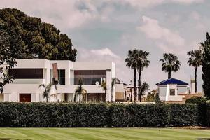 Arecaceae, Espagne, 2020 - Bâtiment en béton blanc près du champ d'herbe verte pendant la journée photo