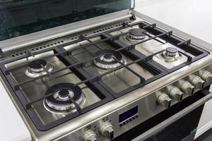 Gros plan d'une cuisinière à gaz neuve et moderne sur comptoir dans une cuisine moderne et contemporaine.