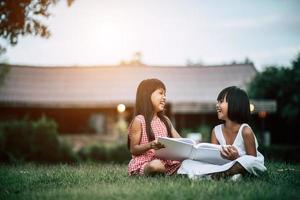 deux petites filles dans le parc sur l'herbe en lisant un livre et en apprenant
