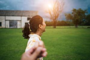 femme qui marche et tenant la main de son petit ami qui la suit photo