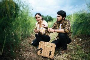 Jeune couple d'agriculteurs récolte des asperges fraîches dans le champ photo