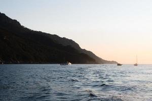 bateaux dans la mer au coucher du soleil photo