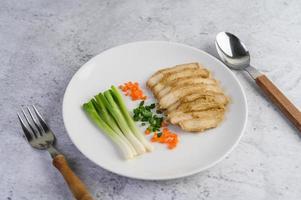 poitrine de poulet cuite à la vapeur avec oignons nouveaux et carottes hachées photo