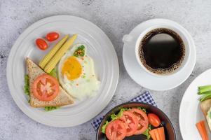 oeufs durs, carottes et tomates avec cuillère et tasse à café