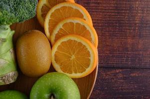Tranches d'orange avec pomme, kiwi et brocoli sur une plaque en bois