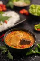 poulet au curry dans une tasse noire avec des nouilles de riz