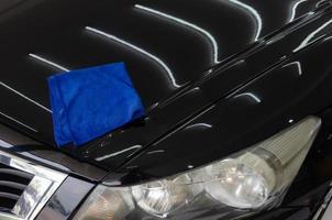 chiffon en microfibre sur le capot d'une voiture noire