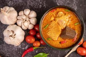poulet au curry dans une tasse noire avec de l'ail et des poivrons photo