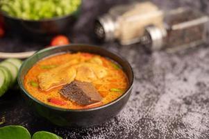 poulet au curry dans une tasse noire avec de l'ail et des poivrons