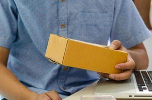 homme tenant une petite boîte en carton