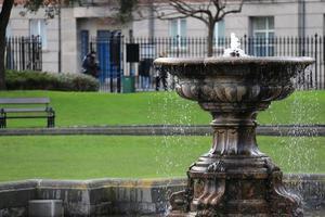 une fontaine d'eau dans un parc herbeux avec des gens en arrière-plan