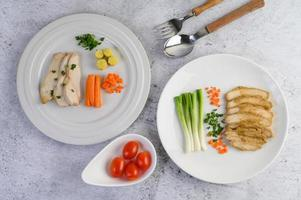 poitrine de poulet cuite à la vapeur sur une assiette blanche avec oignons de printemps et carottes