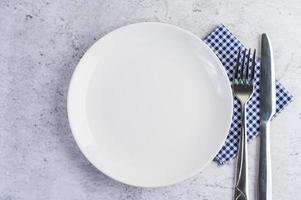 Assiette blanche vide avec une fourchette et un couteau sur une nappe bleu-blanc
