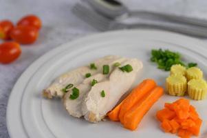 poitrine de poulet cuite à la vapeur sur une assiette blanche avec oignons nouveaux, maïs et carottes