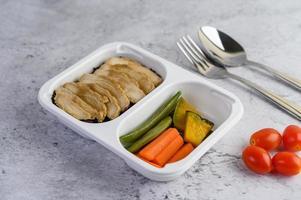 poitrine de poulet cuite à la vapeur dans une boîte en plastique avec citrouille, carottes, haricots et tomate photo