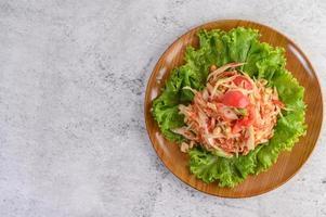 Salade de papaye thaï sur salade dans une assiette en bois photo