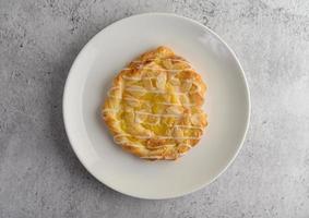 Collation de pain torsadé aux amandes sur une plaque blanche photo