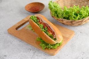 Hot-dog avec laitue et tomate sur une planche à découper en bois