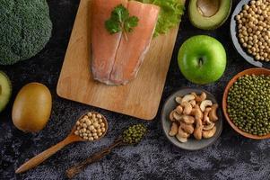 Légumineuses, fruits et saumon sur une planche à découper en bois